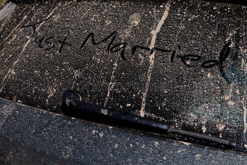 Precis gift scribed av handen på baksidan av en lerig bil på en sol royaltyfri foto
