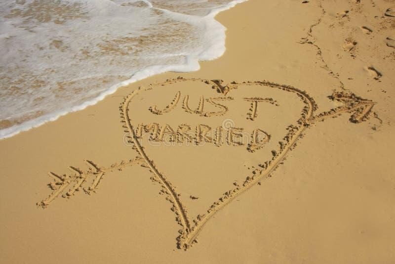 Precis gift skriftligt i sand royaltyfri fotografi