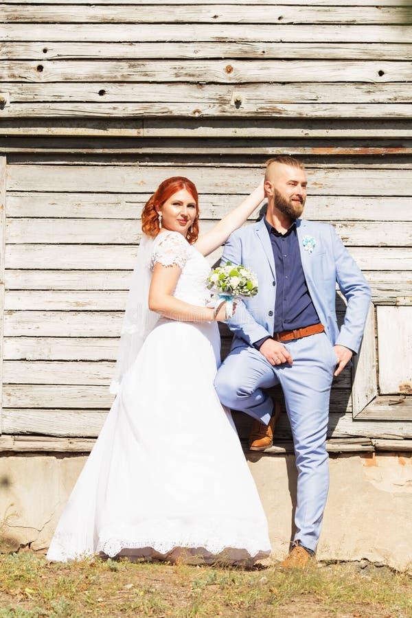 Precis gifta älska hipsterpar i bröllopsklänning- och dräktpos. arkivfoto
