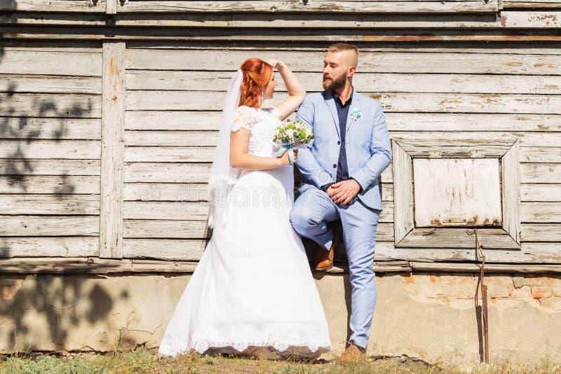 Precis gifta älska hipsterpar i bröllopsklänning- och dräktpos. arkivbilder