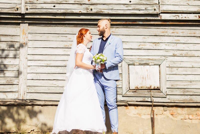 Precis gifta älska hipsterpar i bröllopsklänning- och dräktpos. arkivfoton