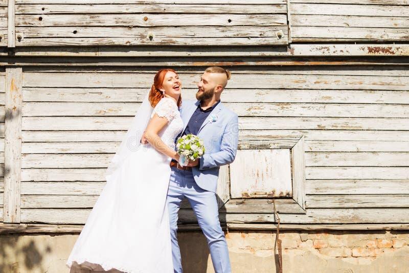 Precis gifta älska hipsterpar i bröllopsklänning- och dräktpos. royaltyfria bilder