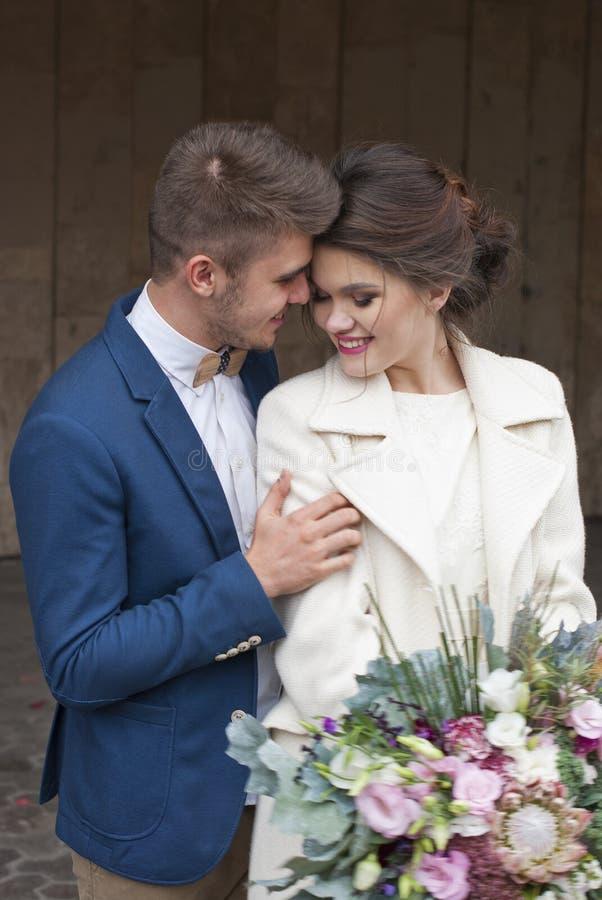 Precis gifta älska par i bröllopsklänning och dräkt som är utomhus- i stadsinställning mot väggen Lyckligt skratta för brud och f royaltyfri fotografi