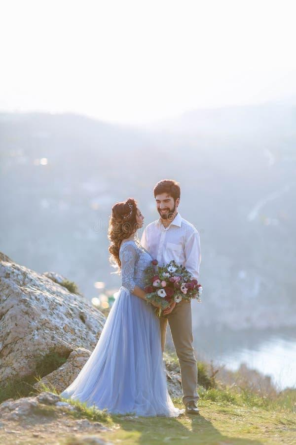 Precis gifta brudgumpar med blommor i händer mot berg över havet Gifta sig bouqet av blommor royaltyfria foton
