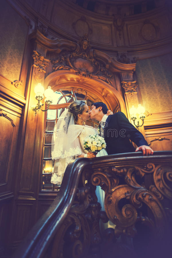 Precis gifta kyssar på trappan i korridoren av den gamla teatern royaltyfria bilder