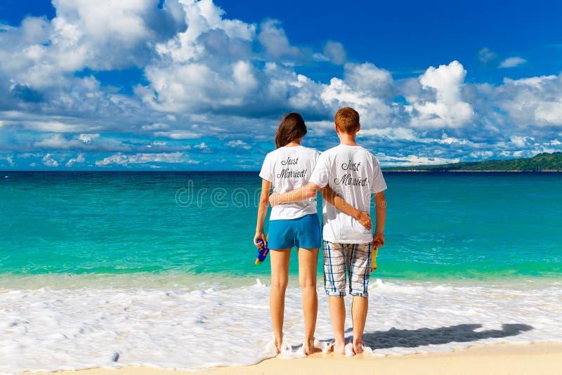 Precis gifta unga lyckliga älska par som har gyckel på tropicaen royaltyfri bild