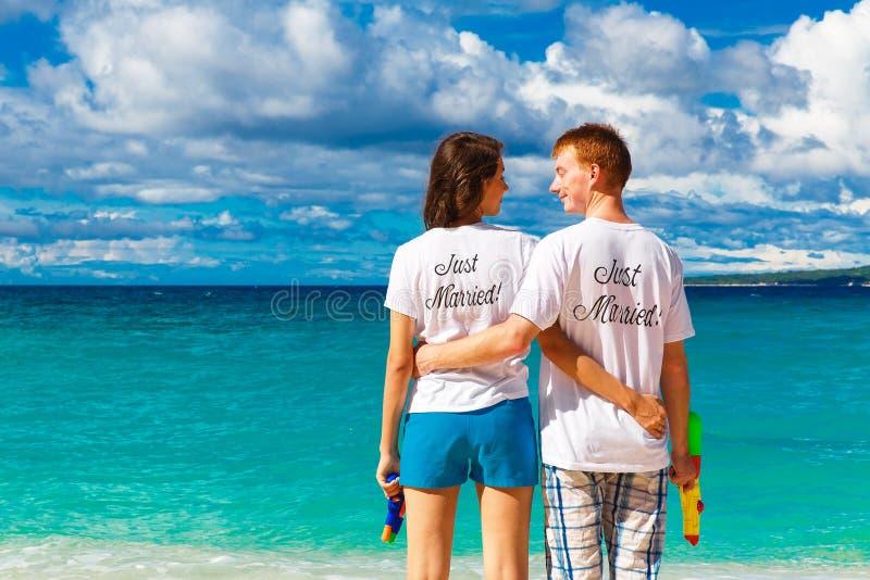 Precis gifta unga lyckliga älska par som har gyckel på tropicaen royaltyfria bilder
