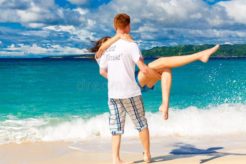 Precis gifta unga lyckliga älska par som har gyckel på tropicaen arkivfoton