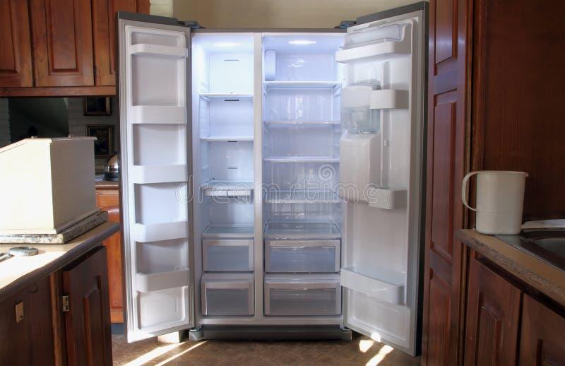 Precis packat upp nytt kylskåp med tomma hyllor arkivbilder