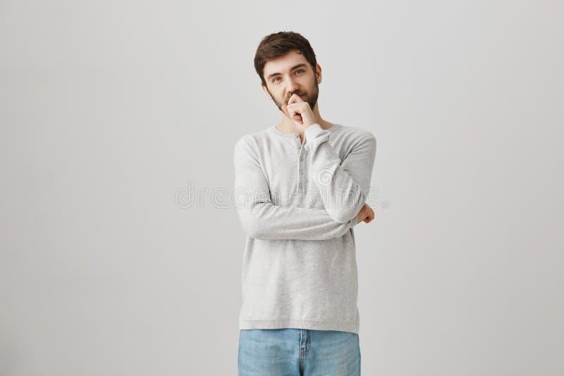 Precisa de fazer a decisão Retrato interno da mão guardando modelo masculina farpada considerável pensativa no queixo e nos bordo fotos de stock royalty free