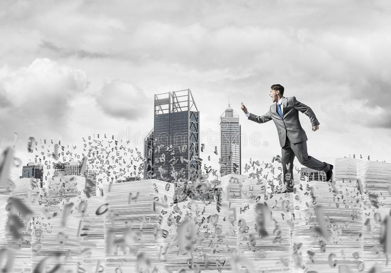 Precise businessman in suit running with phone. royalty free stock image