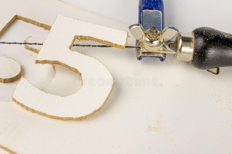 Precise saw for modelers and carpenters on the workshop table. S. Aw with a small blade for cutting complicated shapes. White background royalty free stock photo