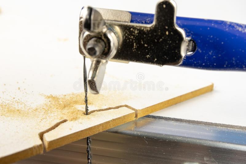 Precise saw for modelers and carpenters on the workshop table. S. Aw with a small blade for cutting complicated shapes. White background royalty free stock photos