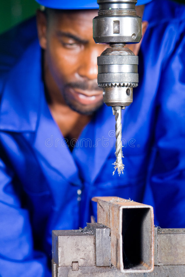 Precision drilling machine. African american machinist operator operating a precision drilling machine stock image