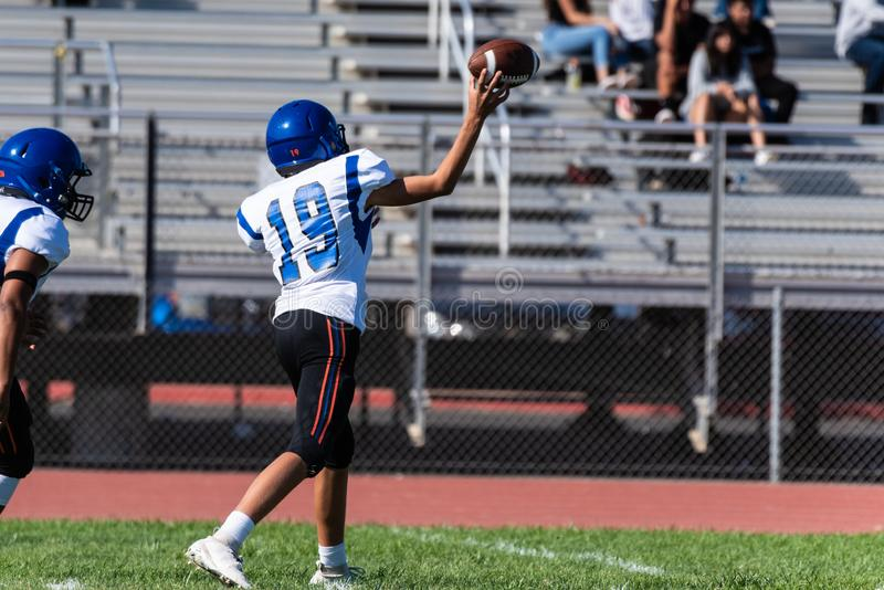 Precision and teamwork working together to win. Football quaterback number nineteen attempts a forward pass during a game with a teammate behind him stock image
