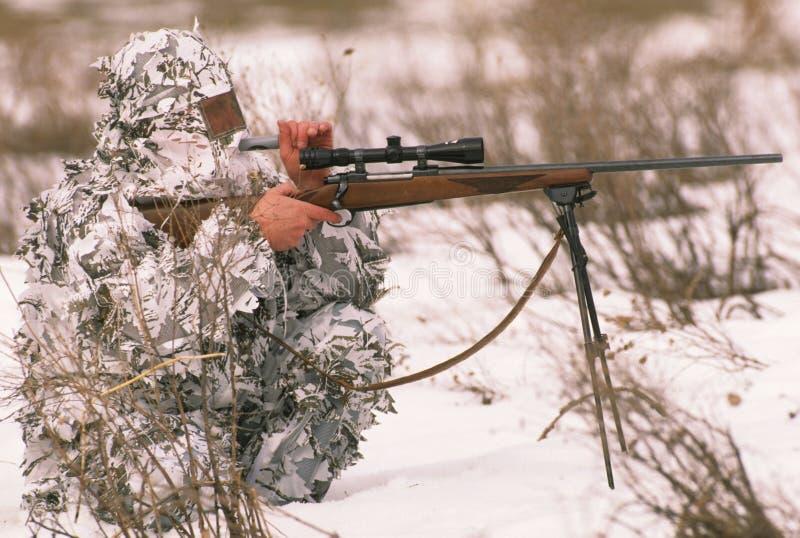 Predator Hunter Calling in Winter. A predator hunter in snow camo calling in winter royalty free stock photos