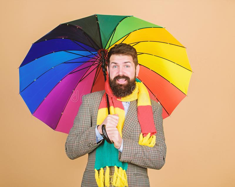 Predict future weather trends. Man bearded guy hold colorful umbrella. It seems to be raining. Rainy days can be tough. To get through. Prepared for rainy day stock image
