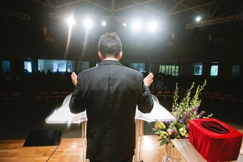 Predikant die voor congregatie bidden stock foto's