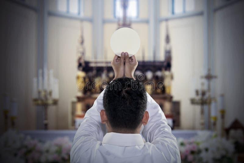 Predikant met sacramenteel brood in de kerk royalty-vrije stock fotografie