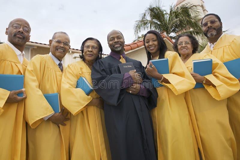 Predikanten och kören i kyrka arbeta i trädgården sikt för låg vinkel för stående royaltyfria foton