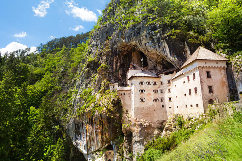 Predjama castle. Panorama of Predjama castle build inside the mountain rocks stock image