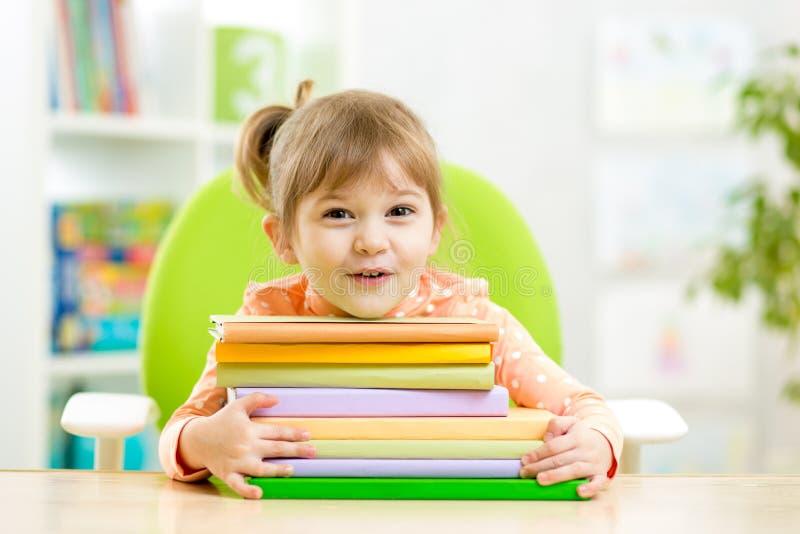 Preescolar lindo de la muchacha del niño con los libros imagenes de archivo