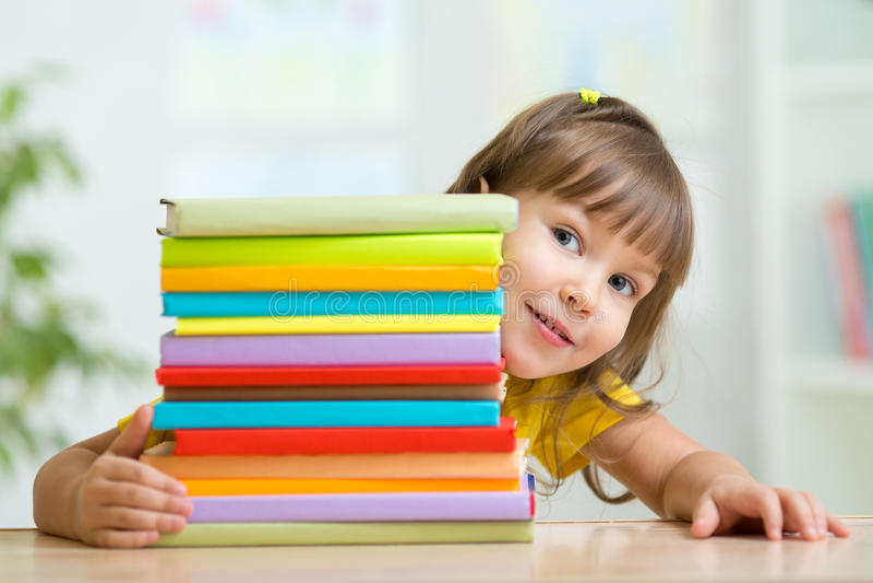 Preescolar lindo de la muchacha del niño con los libros foto de archivo libre de regalías