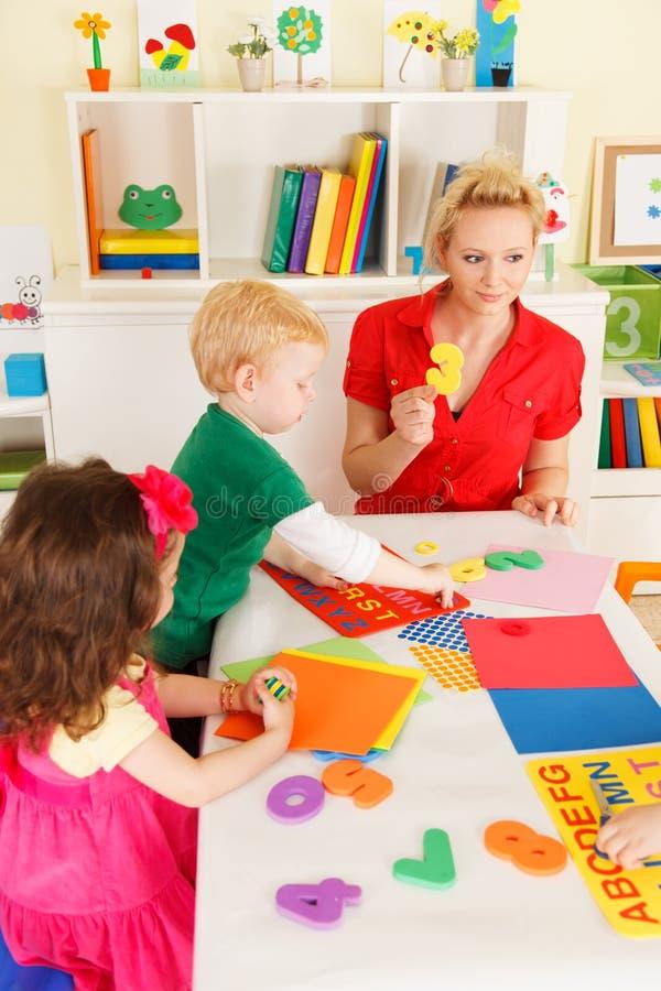 Preescolares en la sala de clase con el profesor imagenes de archivo
