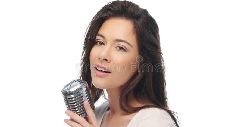 Preety kvinna som sjunger in i en mikrofon arkivbilder