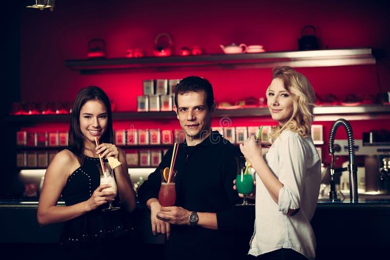 Preety młodzi ludzie piją koktajl w noc klubie fotografia stock