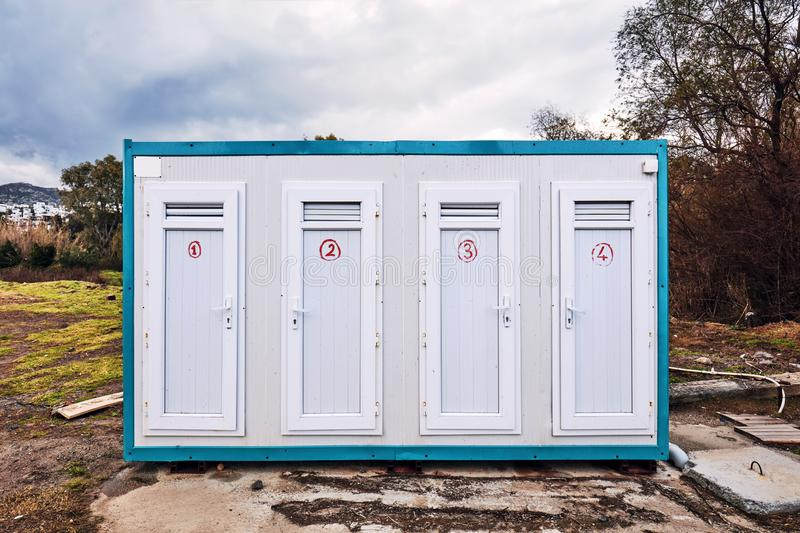 Prefabricated portable cabin with four doors with numbers on them on a meadow field. In the forest royalty free stock photos