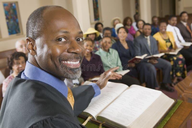 Pregador no altar com a Bíblia que prega ao fim do retrato da assembleia acima foto de stock