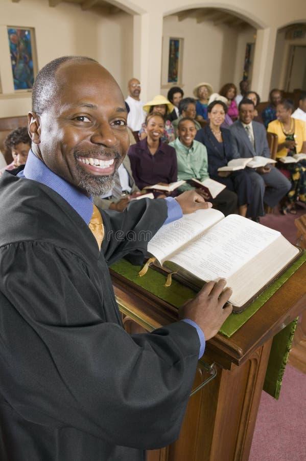 Pregador no altar com a Bíblia que prega ao retrato da assembleia fotografia de stock