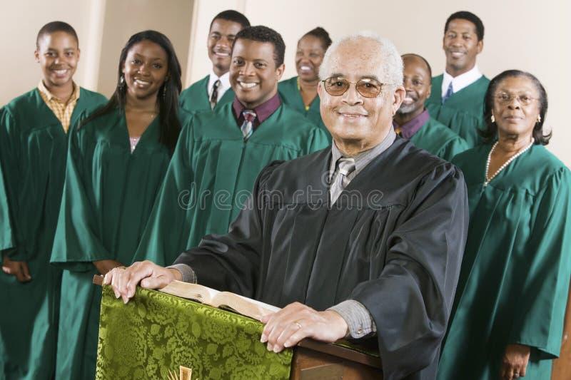 Pregador seguro que está no púlpito com coro no fundo fotografia de stock