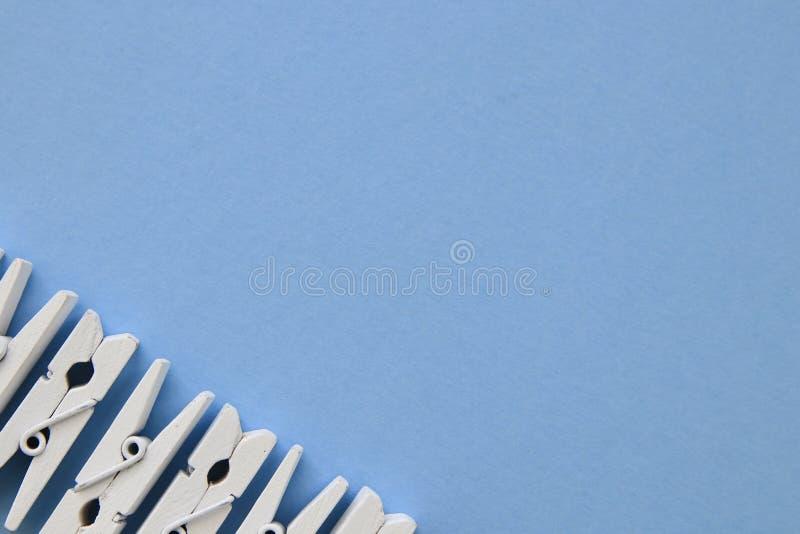 Pregadores de roupa brancos em seguido no fundo azul imagens de stock royalty free