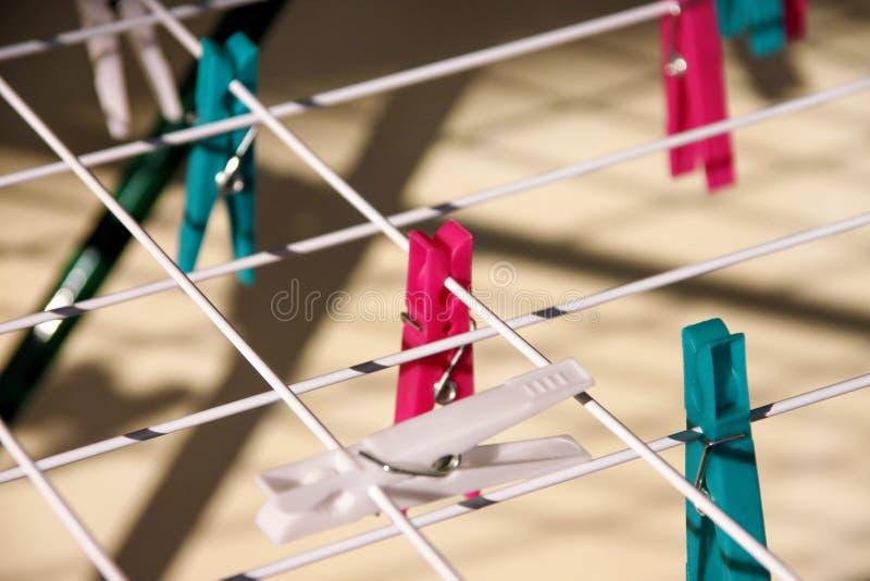 Pregadores de roupa de pano em cremalheira de secagem, foco seletivo Pregadores de roupa plásticos coloridos na corda foto de stock
