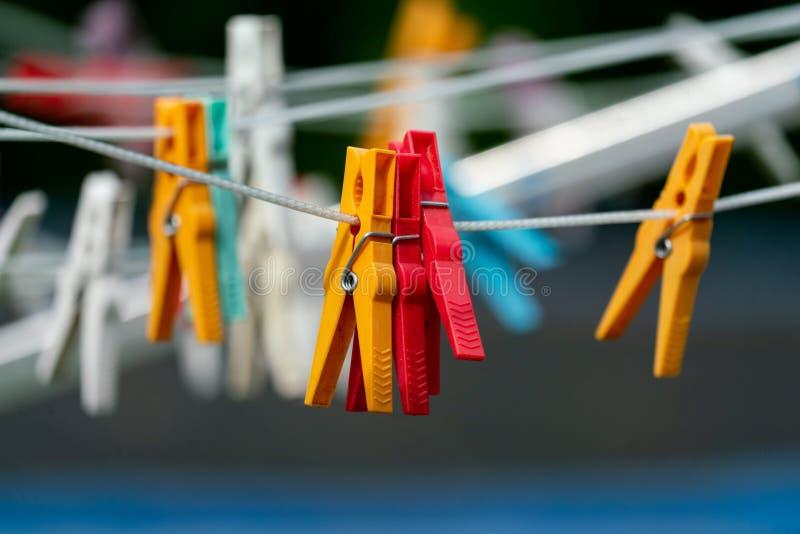 Pregadores de roupa vermelhos e amarelos na linha de lavagem foto de stock royalty free