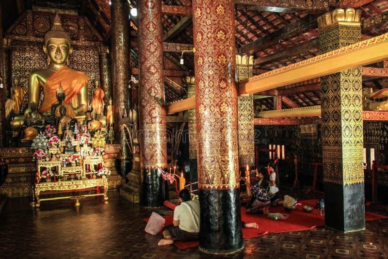 Pregando al tempio di Wat Mai Suwannaphumaham in Luang Prabang, il Laos fotografie stock
