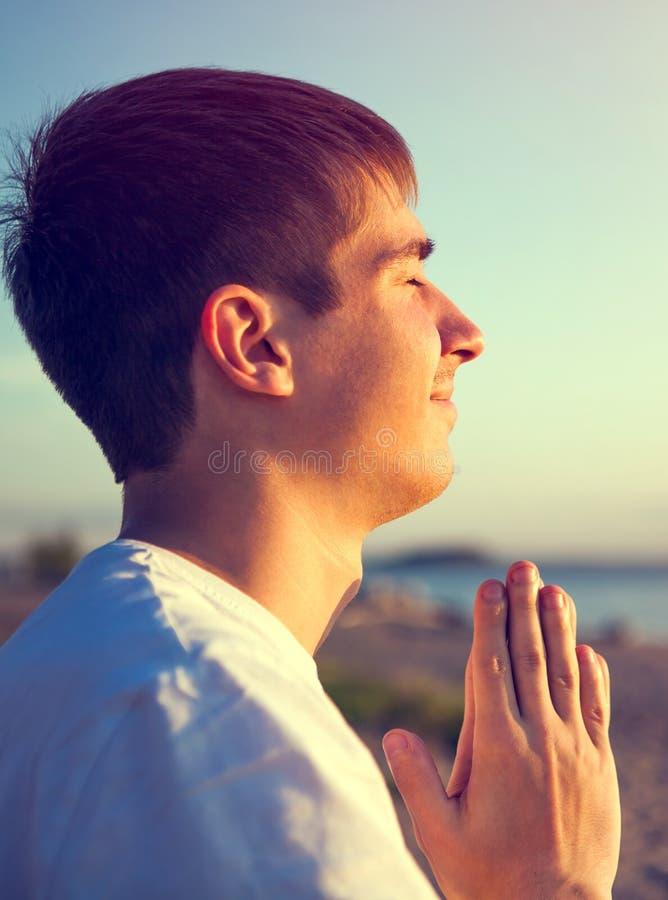 Pregare del giovane all'aperto fotografia stock