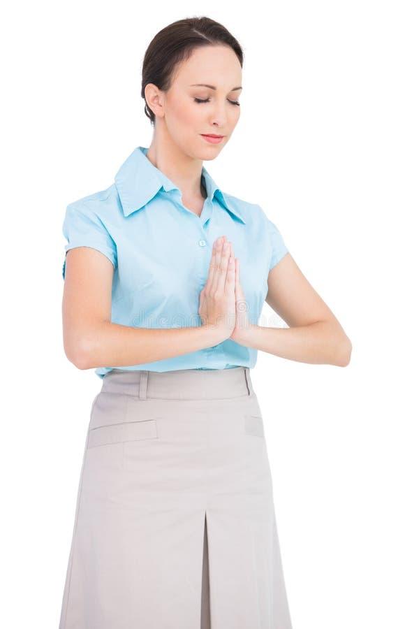 Pregare giovane pacifico della donna di affari fotografia stock
