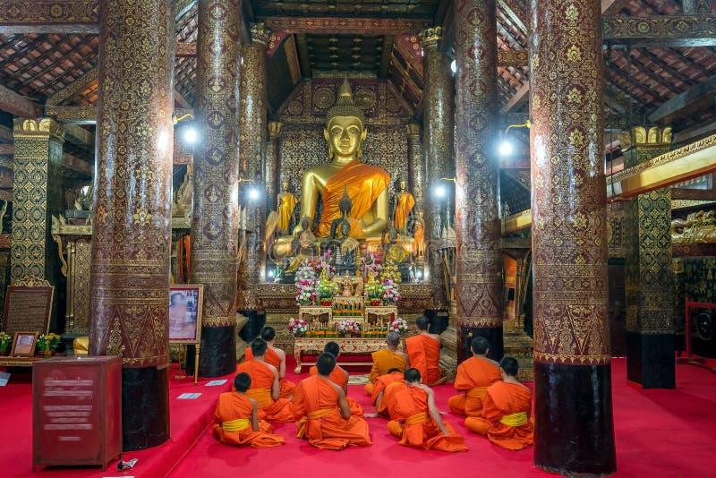 Pregare i monaci al prabang del luang di Wat Xieng Thong immagini stock libere da diritti