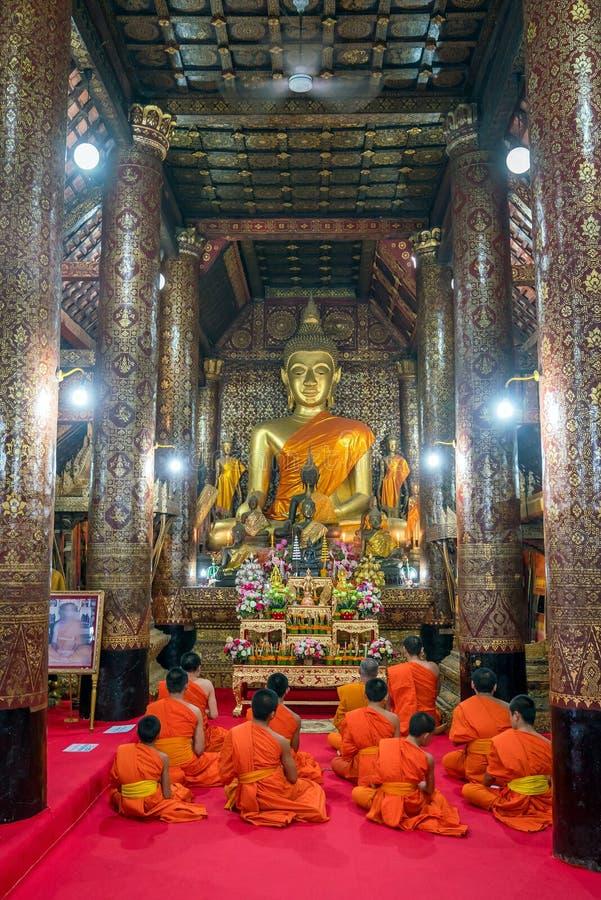 Pregare i monaci al prabang del luang di Wat Xieng Thong immagine stock libera da diritti