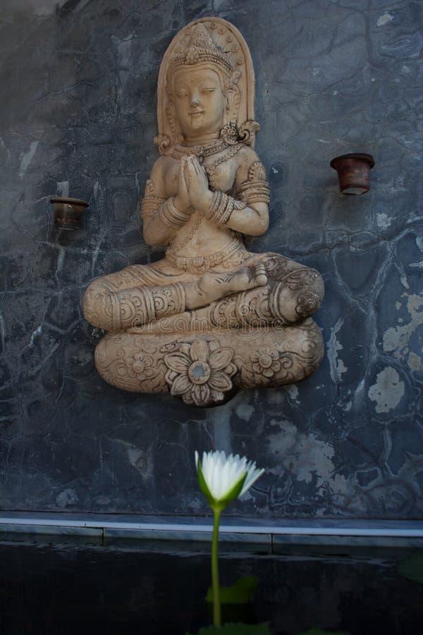 Pregare la statua di Buddha sopra il fiore bianco d'apertura della ninfea fotografie stock libere da diritti