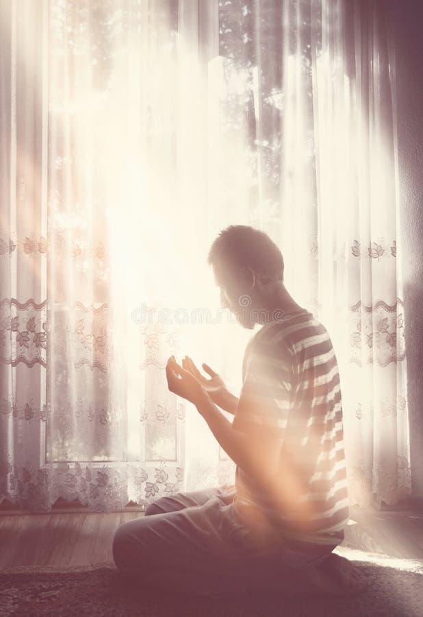Pregare musulmano dell'uomo dell'interno a stanza scura con la luce luminosa della finestra fotografia stock