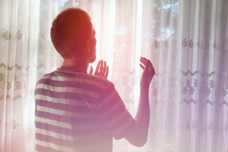 Pregare musulmano dell'uomo dell'interno a stanza scura con la luce luminosa della finestra immagini stock libere da diritti