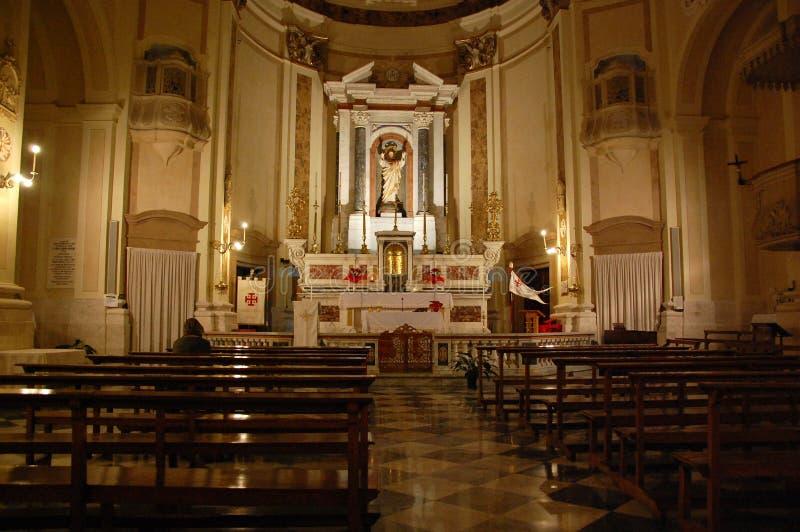 1 Pregare persona, altare, navata laterale, le candele ed i banchi in una cattedrale medievale alla notte Bari, Puglia, Italia de immagine stock