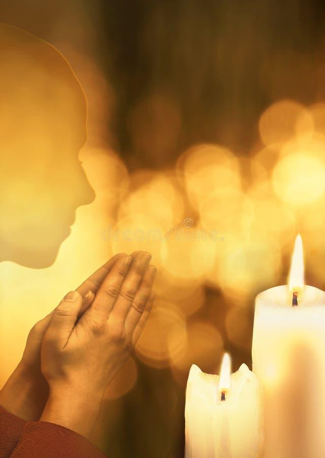 Pregare persona su fondo brillante con le candele brucianti immagini stock libere da diritti