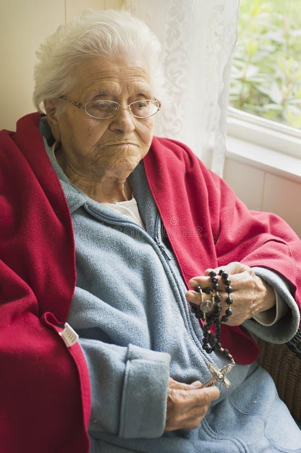 Preghiera anziana della donna immagine stock