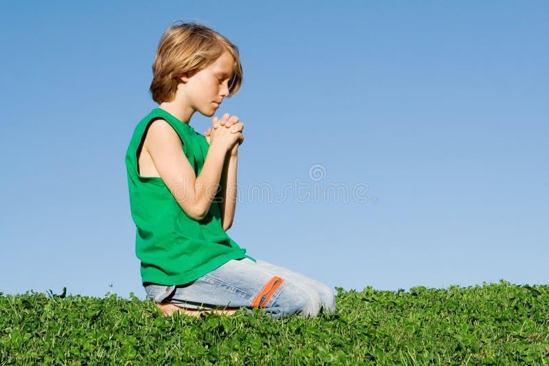 Preghiera cristiana di inginocchiamento del bambino immagini stock