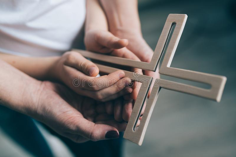 Preghiera della famiglia con l'incrocio di legno fotografie stock